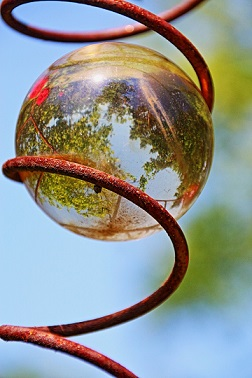 downward spiral with glass ball inside reflecting topsy turvy world garden